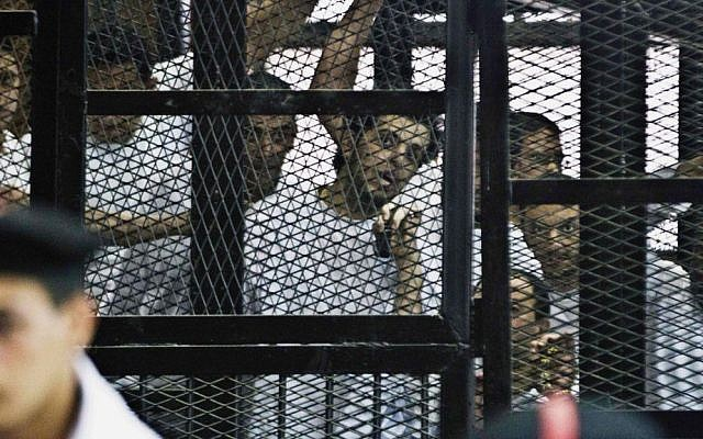 Al-Jazeera's Egyptian journalist Abdullah Elshamy, center, appears in a defendants' cage along with several other defendants in a courthouse during a trial on terror charges in Cairo. Egypt's Prosecutor General ordered release of Al-Jazeera journalist who has been on hunger strike for more than 100 days to protest his prolonged detention without trial. (photo credit: AP Photo/Hamada Elrasam)