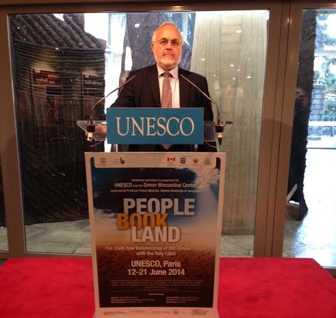 Simon Wiesenthal Center's Rabbi Abraham Cooper speaks from a podium featuring the new poster for the exhibit, with the reference to the Land of Israel replaced by the Holy Land, June 11. (photo credit: Courtesy Simon Wiesenthal Center)