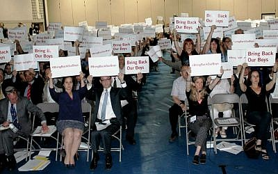 Attendees at a rally in Toronto in support of kidnapped Israeli teens, including Israeli Consul DJ Schneeweiss (center left), hold  up #BringBackOurBoys signs in English and Hebrew for photos to be sent to the teens' families. (Courtesy UJA Federation of Greater Toronto)