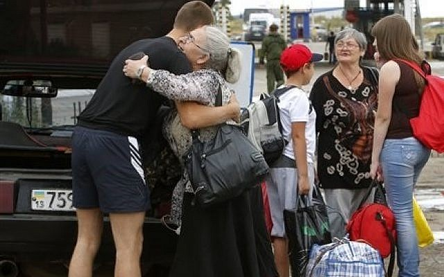 A man says goodbye to his relatives as they prepare to cross the border into Russia at the Ukrainian-Russian border checkpoint in Izvaryne, Luhansk region, eastern Ukraine Thursday, June 26, 2014. (photo credit: AP Photo/Dmitry Lovetsky)