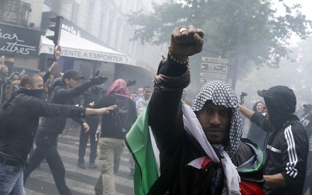 A protester wearing a kaffiyeh and wrapped in a Palestinian flag raises his fist on July 13, 2014 in Paris, during a demonstration against Israel and in support of residents in the Gaza Strip. (photo credit: AFP/KENZO TRIBOUILLARD)