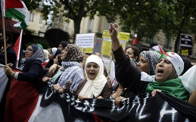 Women hold a banner as they take part in a demonstration against Israel and in support of residents in the Gaza Strip,  on July 13, 2014, Paris. (photo credit: AFP/ KENZO TRIBOUILLARD)