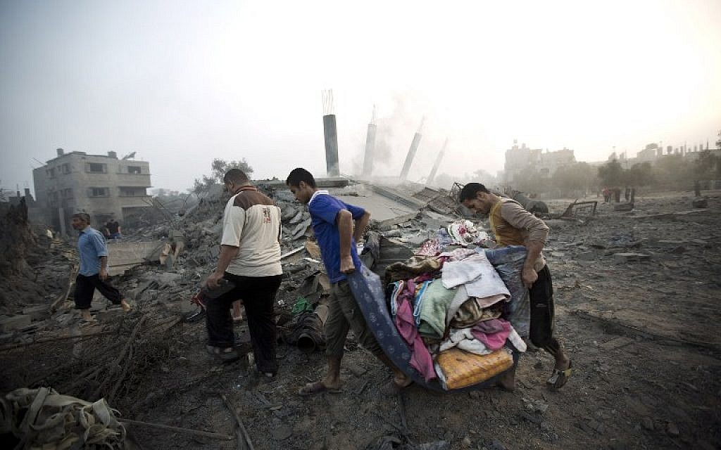 Palestinians collect their belongings from damaged houses after an Israeli missile strike hits Gaza City on July 8, 2014 (photo credit: AFP/MAHMUD HAMS)