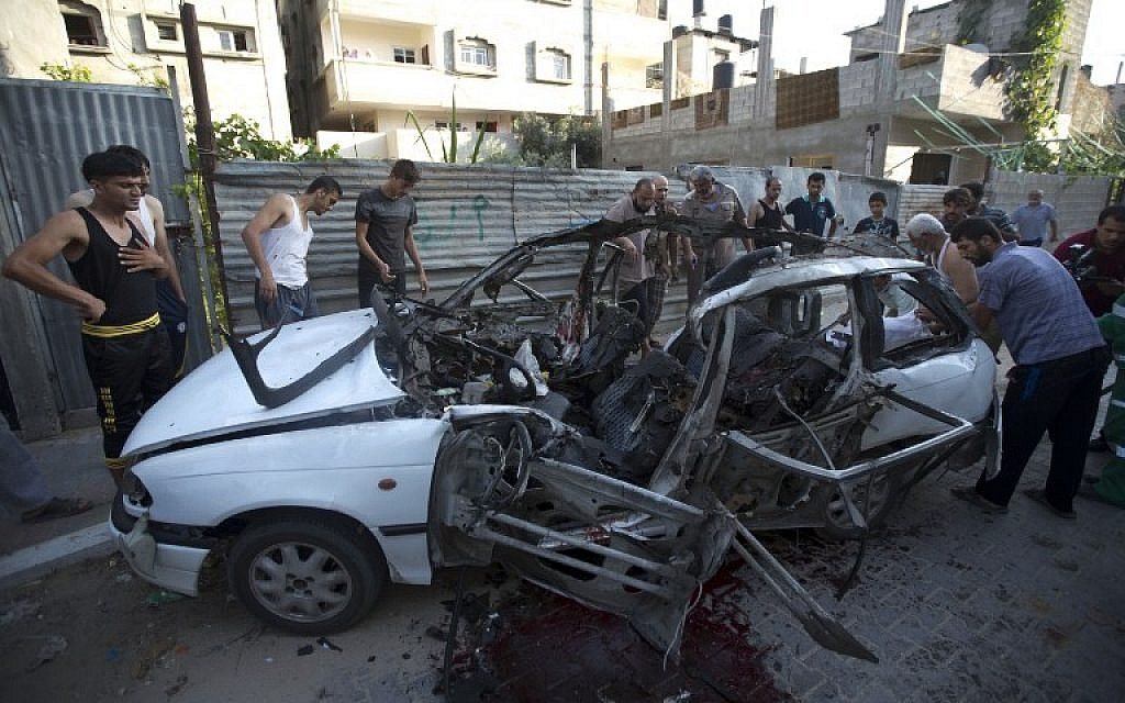Palestinians inspect the wreckage of a car hit by an Israeli air strike in Gaza City, killing three Islamic Jihad men,according to the IDF, on July 10, 2014. (photo credit: AFP/ MAHMUD HAMS)
