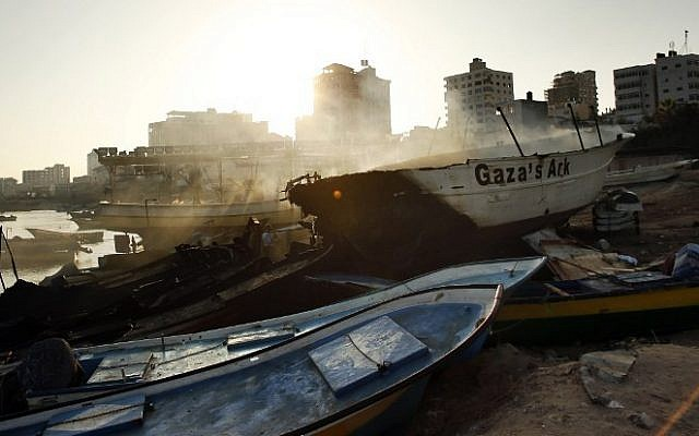 Smoke rises as the peace activist boat 'Gaza's Ark' smolders at sunrise following an Israeli airstrike on Gaza harbor, Friday, July 11, 2014 in Gaza City. (photo credit: Thomas Coex/AFP)