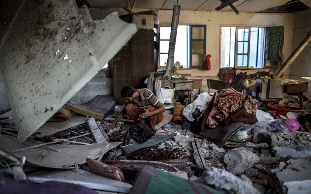 A Palestinian looks for human remains in a classroom inside a UN school in Gaza City after the area was hit by shelling, July 30, 2014. (photo credit: AFP/Marco Longari)
