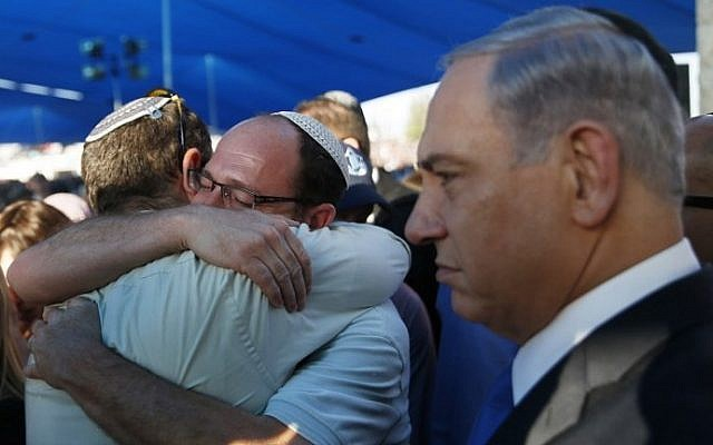 Israeli Prime Minister Benjamin Netanyahu, right, stands next to Avi Fraenkel, left, and Ofir Shaar (2nd left), fathers of two of the three Israeli teenagers killed in the West Bank, during their funeral on July 1, 2014 in the cemetery of Modiin in central Israel. (photo credit: AFP/POOL/BAZ RATNER)