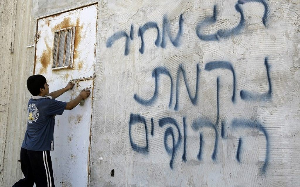 Illustrative: A Palestinian boy opens a door after Hebrew graffiti was daubed on a wall, allegedly by Jewish settlers, in the village of Aqraba, in the West Bank, close to the city of Nablus, on July 2, 2014 (AFP/JAAFAR ASHTIYEH)