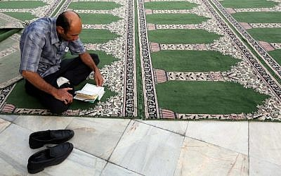 Illustrative photo of a Muslim man reading the Quran  during the holy month of Ramadan (photo credit: Atta Kenare/AFP)