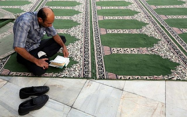 A Muslim man reads the Quran on July 2, 2014, during the holy month of Ramadan. Across the Muslim world, the faithful fast from dawn to dusk, and abstain from eating, drinking, smoking and having sex during that time as they strive to be more pious and charitable. (photo credit: Atta Kenare/AFP)