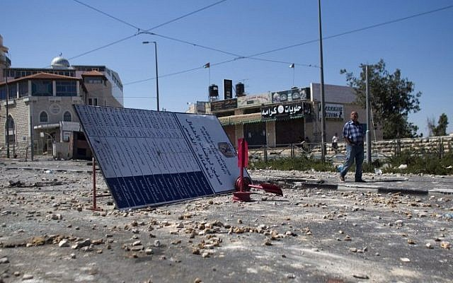 A man walks on a street covered with stones on July 3, 2014, in Jerusalem following clashes between Palestinians and Israeli security forces near the house of a slain Palestinian youth. (photo credit: Ahmad Gharabli/AFP)