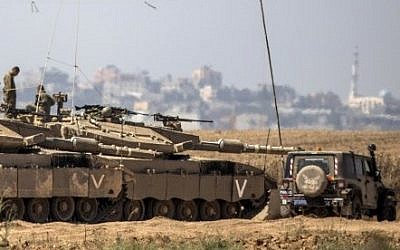 Israeli soldiers sit atop their tanks on the Israeli side of the border with the Gaza Strip, on July 3, 2014 (Jack Guez/AFP)