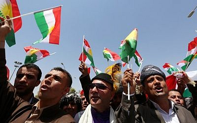 Iraqi Kurdish protesters wave flags of their autonomous Kurdistan region during a demonstration to claim for its independence on July 3, 2014, outside the Kurdistan parliament building in Arbil, in northern Iraq. (photo credit: AFP/Safin Hamed)