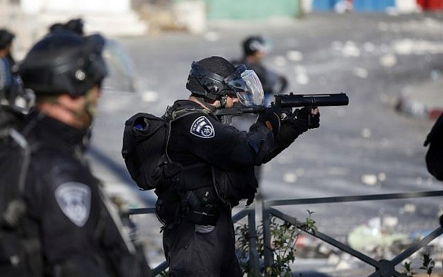An Israeli policeman prepares to fire sponge projectiles towards protesters during clashes in Shuafat, East Jerusalem on July 4, 2014 (Photo credit: Thomas Coex/AFP)