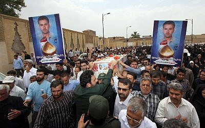 """A handout image made available by Iran's FARS News Agency on July 5, 2014, shows mourners attending the funeral of an Iranian pilot at a mosque in the city of Shiraz, on July 4, 2014. According to state media, the pilot, Colonel Shoja'at Alamdari Mourjani, was killed while """"defending"""" Shiite Muslim holy sites in the city of Samarra, north of Baghdad, Iraq, in what is thought to be Tehran's first military casualty during battles against Islamic State jihadists. (photo credit: AFP/HO/Fars News/Amin Faezi)"""
