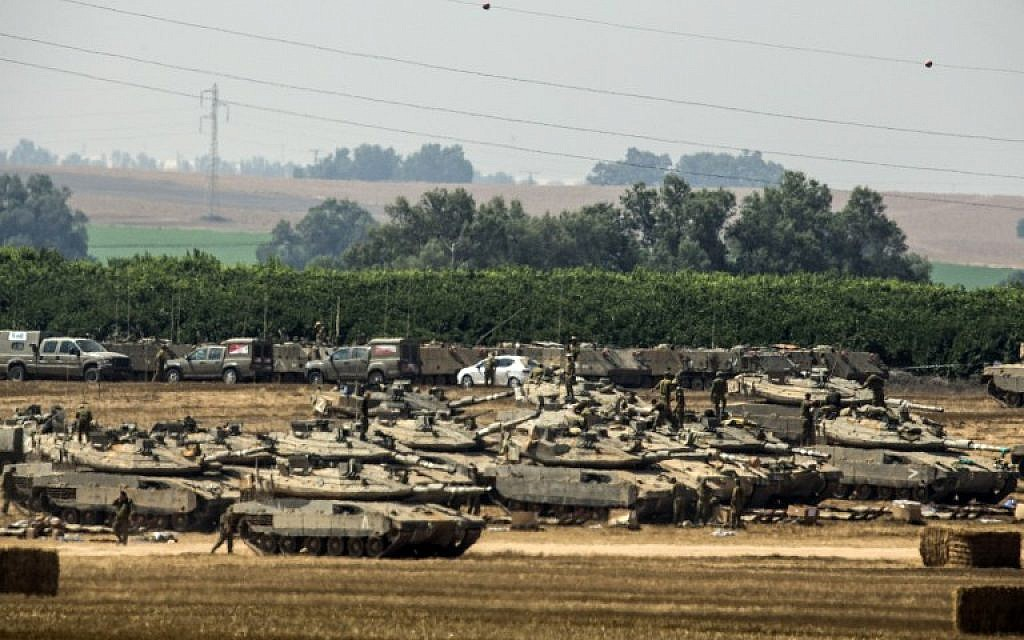 Israeli soldiers stand next to Merkava tanks positioned on the Israeli side of the border with the Gaza Strip on July 7, 2014. ( photo credit: AFP/JACK GUEZ)