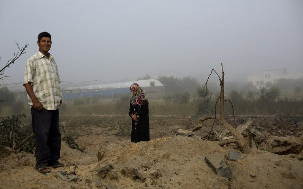 A Palestinian man and a woman inspect the site of an Israeli military strike in Khan Yunis, in the southern Gaza Strip, on July 08, 2014 (photo credit: AFP/MOHAMMED ABED)