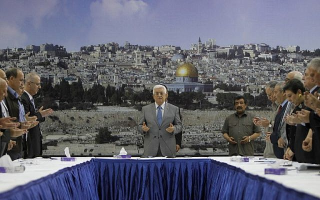 Palestinian Authority President Mahmoud Abbas (C) prays prior a meeting with his leadership in the West Bank city of Ramallah on July 9, 2014  (photo credit: AFP/ABBAS MOMANI)