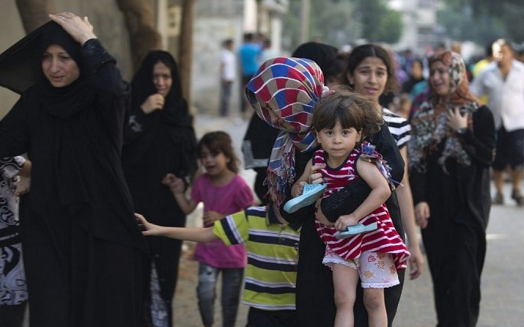 Palestinian families leave their houses following overnight Israeli airstrikes on Gaza City on July 10, 2014. (photo credit: AFP/Mohammed Abed)