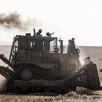 Illustrative. An Israeli D9 bulldozer rolls along the southern Israeli border with the Gaza Strip following Israeli airstrikes on the Gaza Strip on July 10, 2014. (Jack Guez/AFP)
