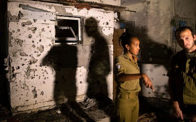 Israeli soldiers inspect the damage caused to a house in the southern Israeli city of Beersheba after it was hit by a rocket fired from the Gaza Strip on Thursday, July 10, 2014. (photo credit: Menahem Kahana/AFP)