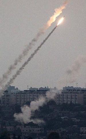 A picture taken from the southern Israeli Gaza border shows a rocket being launched from the Gaza strip into Israel on Friday, July 11, 2014. (photo credit: Menahem Kahana/AFP)