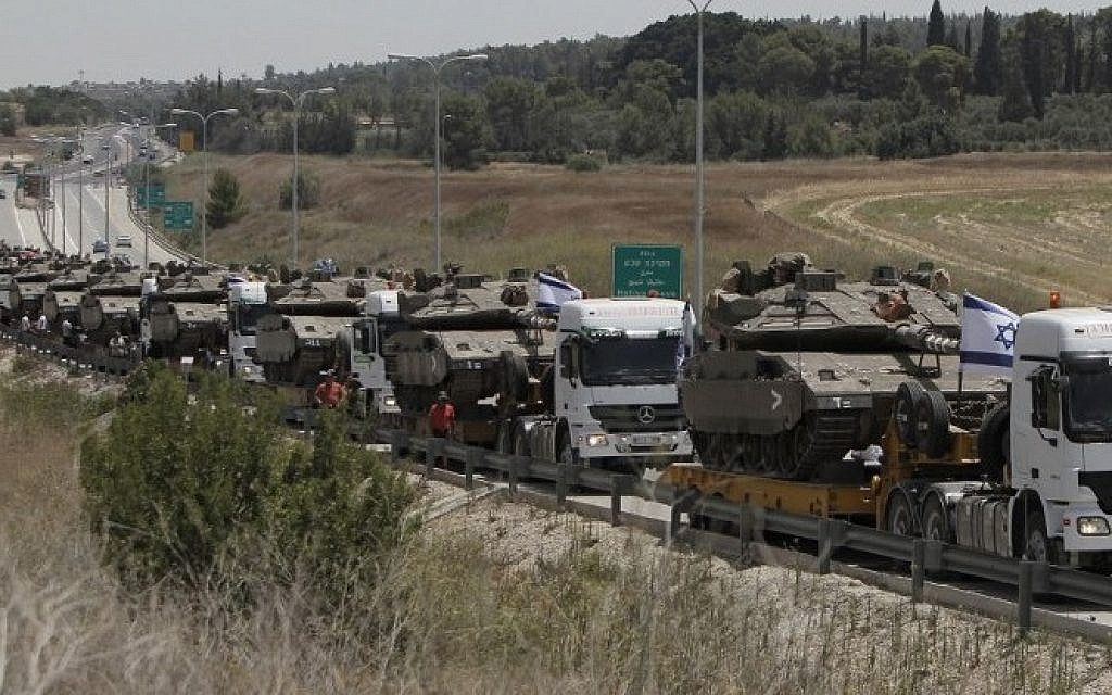 Trucks transport IDF tanks on a road leading to southern Israel, on July 12, 2014, as Israel warns of a possible ground operation in the Gaza Strip (Photo credit: Ahmad Gharabli/AFP)