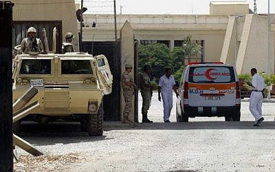 Egyptian security forces stand guard as an ambulance, carrying a Palestinian who was wounded in an Israeli air strike, crosses the Rafah crossing between Egypt and the southern Gaza Strip on July 12, 2014. (photo credit: AFP/SAID KHATIB)