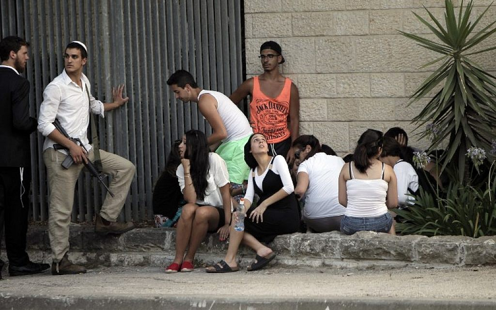 Israelis take cover in Jerusalem on July 12, 2014, during a rocket attack by Palestinian militants from the Gaza Strip. (photo credit: AFP/Ahmad Gharabli)