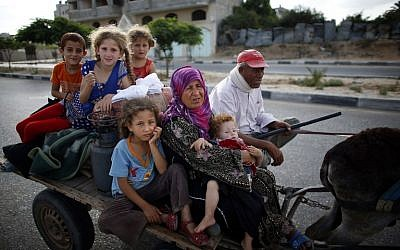 Palestinian families travel to a UN school in Gaza City to seek shelter after evacuating their homes in the northern strip, on Sunday, July 13, 2014 (photo credit: AFP/THOMAS COEX)