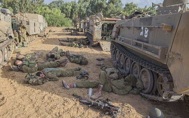 Israeli soldiers from the Nahal Infantry Brigade rest in the shade of their armored vehicle at an Israeli army deployment area near Israel's border with the Gaza Strip, on July 15, 2014.  (photo credit: AFP / JACK GUEZ)