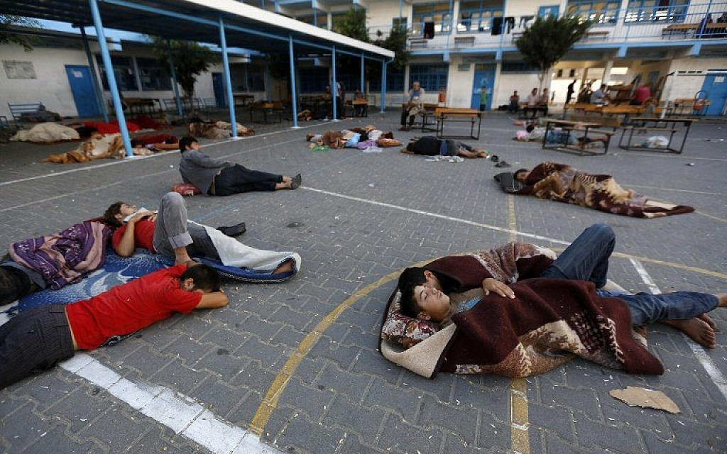 Palestinians sleep in the yard of a UN school in the northern Gaza Strip town of Beit Lahiya early on July 16, 2014, after evacuating their houses near the border with Israel. (photo credit: AFP/MOHAMMED ABED)