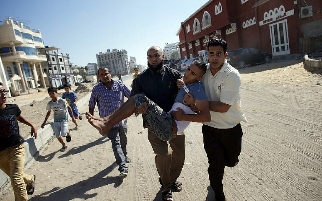 Palestinian employees of Gaza City's al-Deira hotel carry a wounded boy following an Israeli military strike near on the beach, on July 16, 2014. Four children were killed in Gaza City during the attack. (photo credit: AFP/THOMAS COEX)
