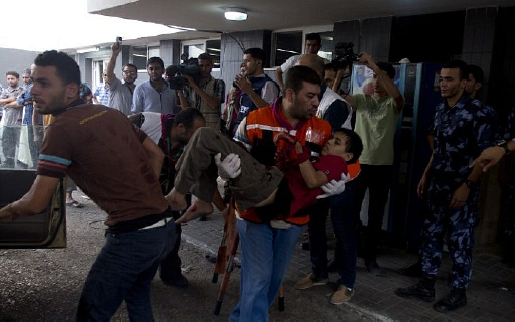 An injured Palestinian boy is carried into at Shifa hospital in Gaza City on Sunday, July 20, 2014 (photo credit: AFP/MAHMUD HAMS)
