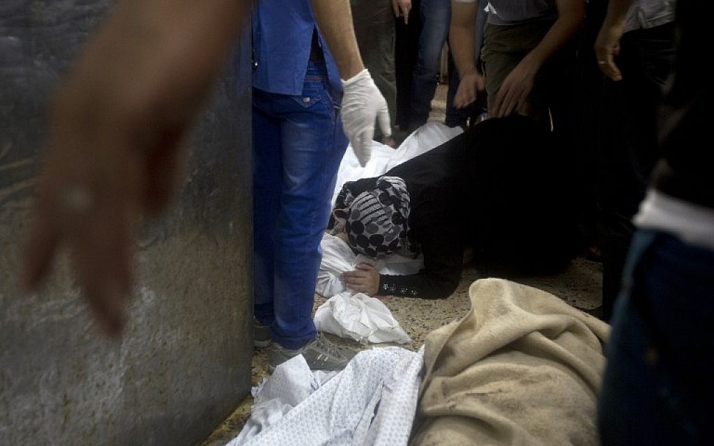 A woman grieves over a body lying on the ground of the morgue of the al-Shifa hospital in Gaza City, on July 20, 2014. (photo credit: AFP/MAHMUD HAMS)
