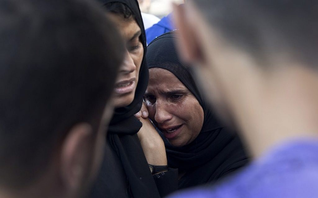 Palestinians grieve over the death of relatives as they wait outside the morgue of the al-Shifa hospital in Gaza city, on July 21, 2014. (photo credit: AFP/MAHMUD HAMS)