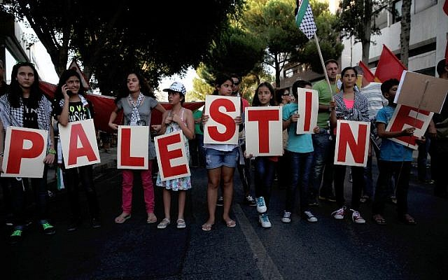 Protesters hold placards painted with letters forming the word 'Palestine' during a demonstration near the Israeli Embassy in the Cypriot capital, Nicosia, against Israel's military offensive on the Gaza Strip, on July 21, 2014. (photo credit: AFP/Yiannis Kourtoglou)