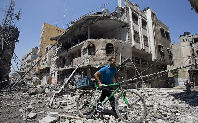 A Palestinian man pushes his bicycle amidst debris following an Israeli military strike in Gaza city, on July 23, 2014. (photo credit: AFP/ MAHMUD HAMS)