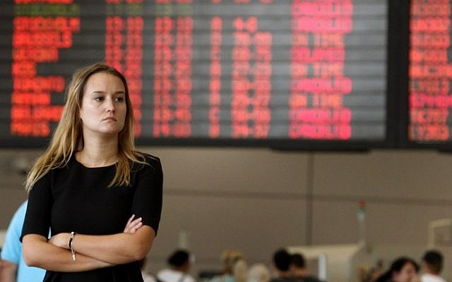 A traveler stands in front of a departure time flight board displaying various cancellations at Ben Gurion Airport on Wednesday, July 23, 2014. (photo credit: Gil Cohen-Magen/AFP)