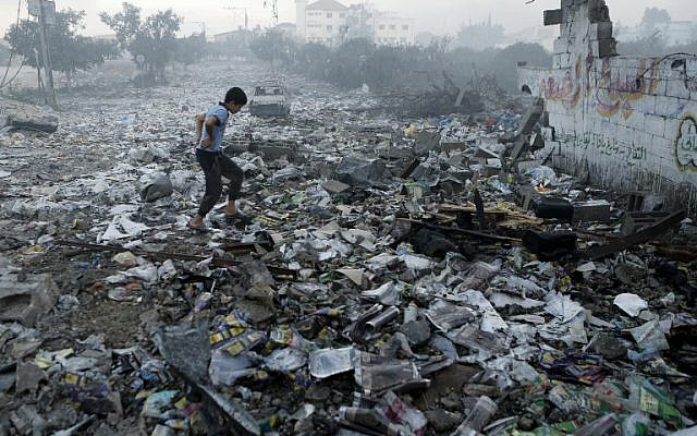 A Palestinian youth walks on debris as he inspects damages following an Israeli air strike in Gaza City, on July 24, 2014 (photo credit: AFP/MOHAMMED ABED)
