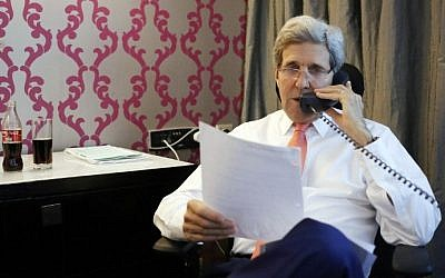 US Secretary of State John Kerry (R) talks to Prime Minister Benjamin Netanyahu (on the phone) on July 25, 2014, from his hotel room in the Egyptian capital, Cairo (photo credit: AFP/Pool)