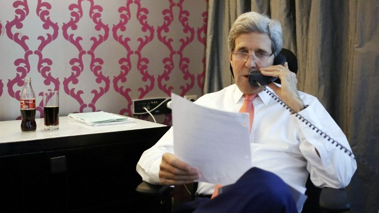 US Secretary of State John Kerry (R) talks to Prime Minister Benjamin Netanyahu (on the phone) on July 25, 2014, from his hotel room in the Egyptian capital, Cairo. (photo credit: AFP/Pool)