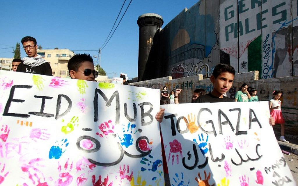 Young Palestinians hold placards reading 'Eid Mubarak to Gaza' (Happy Eid to Gaza) during a demonstration in solidarity with the children killed in the Gaza Strip, on Monday, July 28, 2014, in the Aida Palestinian refugee camp near the West Bank city of Bethlehem (photo credit: AFP/MUSA AL SHAER)