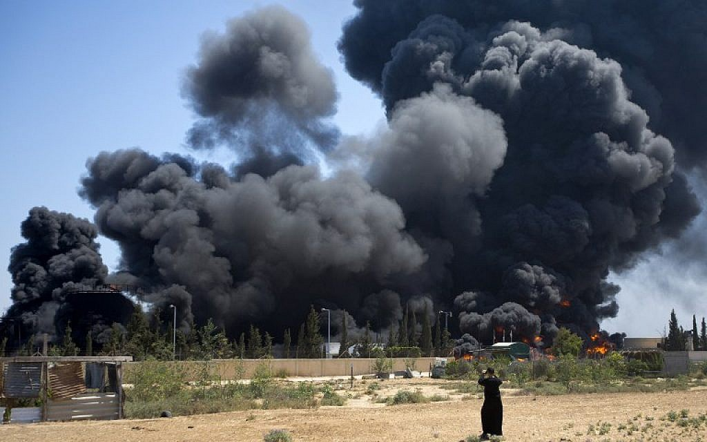 A Palestinian man looks on as flames engulf the fuel tanks of the only power plant supplying electricity to the Gaza Strip after it was hit on July 29, 2014,  (photo credit: AFP/MAHMUD HAMS)