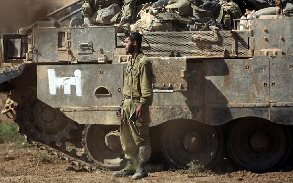 An Israeli soldier prays next to an armored personnel carrier near the Israel-Gaza border, on July 30, 2014. (photo credit: AFP/DAVID BUIMOVITCH)