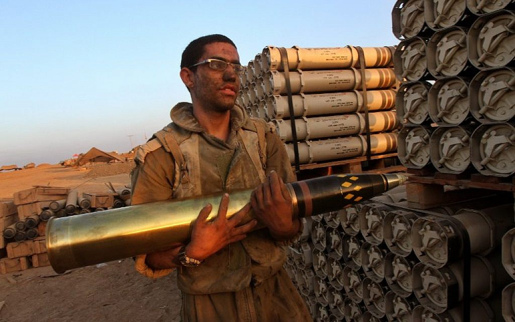 An Israeli soldier carries a shell as troops prepare munitions along the border between Israel and the Hamas-controlled Gaza Strip on July 30, 2014.  (photo credit: AFP/GIL COHEN-MAGEN)