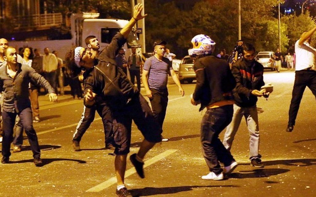 Demonstrators throw stones at the Israeli Embassy in Ankara, as they protest against Israel's military action in Gaza, on July 18, 2014. (photo credit: AFP/Adem Altan)
