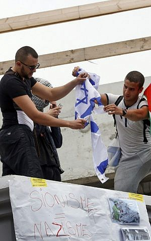 "Protesters burn an Israeli one on a rooftop where is hung a placard reading ""zionism = nazism"" as they gather near the Barbes-Rochechouart aerial metro station prior to the departure of a demonstration, banned by French police, in Paris on July 19, 2014. (photo credit: AFP/Francois Guillot)"