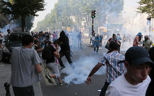 Protesters run as they clash with police near the Barbes-Rochechouart aerial metro station prior to the departure of a demonstration, banned by French police, in Paris on July 19, 2014. (photo credit: AFP/Jacques Demarthon)