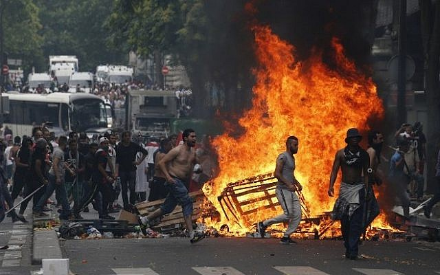 Protesters run by a fire barricade near the aerial metro station of Barbes-Rochechouart, in Paris, on July 19, 2014, during clashes with French riot police in the aftermath of a demonstration, banned by French police, to denounce Israel's military campaign in Gaza. Photo credit: AFP/ FRANCOIS GUILLOT)